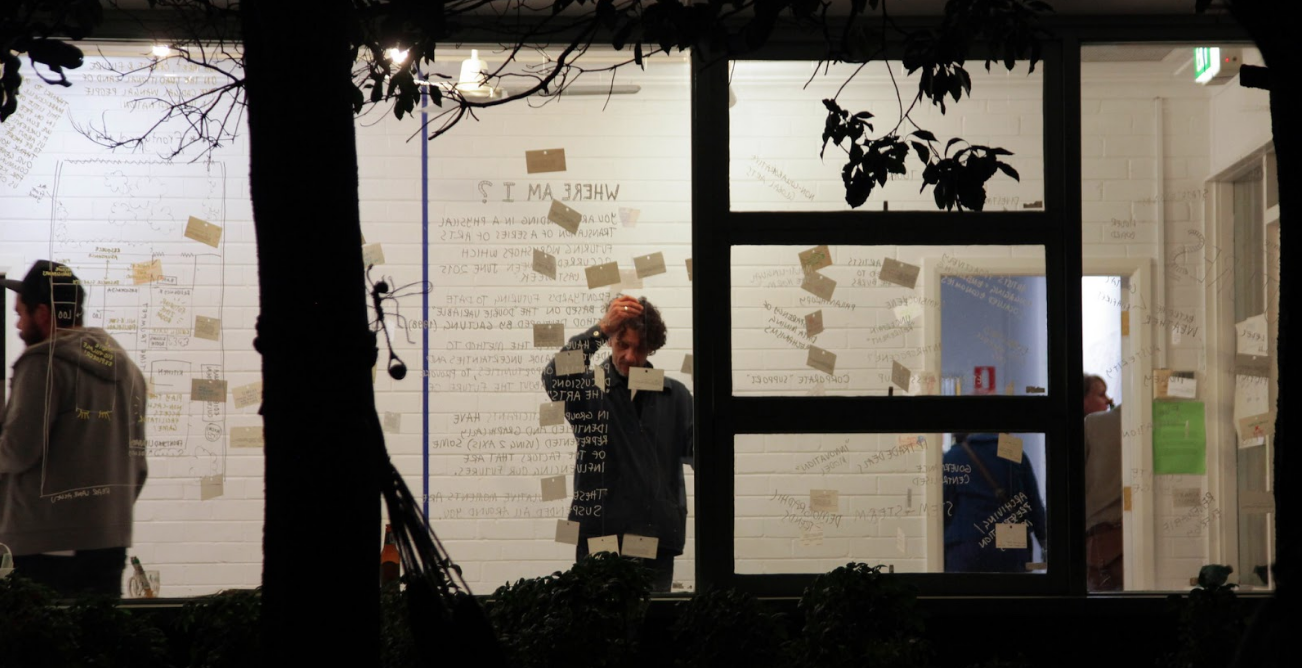 Photograph of the front room of Frontyard. Cards are suspended from the roof across a room, and people look at them, thinking about what the future described might be like.